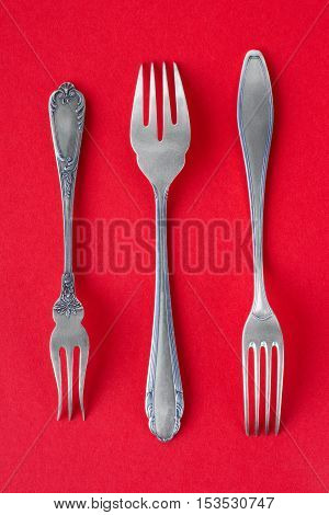 Ancient silver fork set on red background. Group of three different victorian sterling silver forks end of 19th century