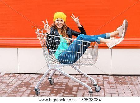 Fashion Pretty Cool Girl In Trolley Cart Having Fun Wearing Black Jacket Hat Over Colorful Orange Ba