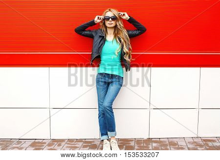 Fashion Pretty Woman Model In Sunglasses Black Rock Jacket Posing At City Over Red Background
