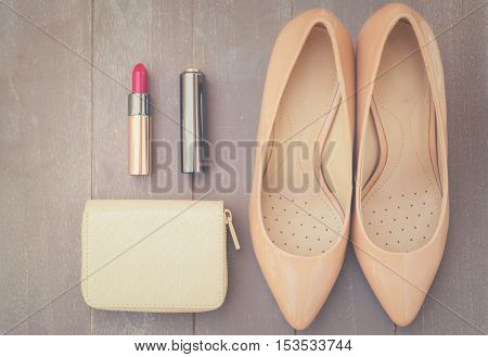 Nude colored high heels still life with wallet and red lipstick, top view, retro toned