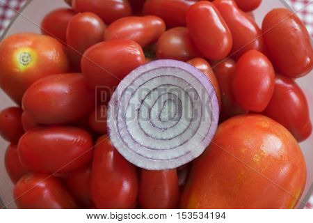 Tropea onion cut half on background of tomatoes