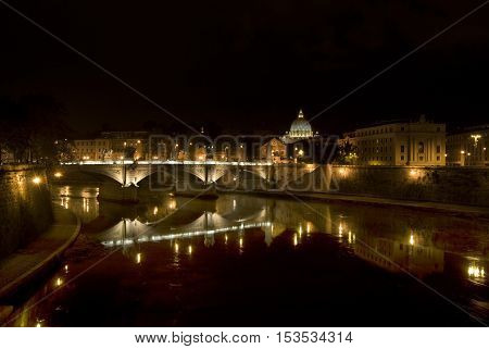 reflections of Rome by night in the tiber river