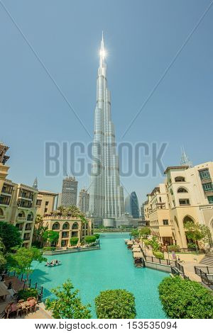 DUBAI, UAE - OCTOBER 11, 2016: A view of Souk al Bahar and the turquoise Burj Khalifa in a Lake surrounded by greenery