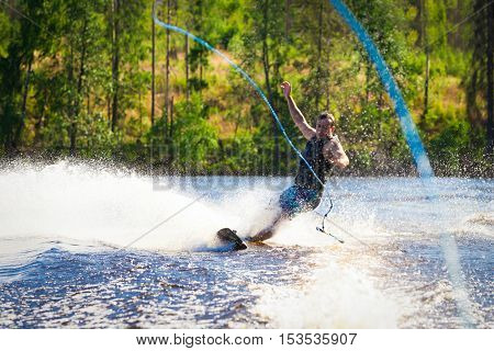 Young man riding wakeboard on a summer lake
