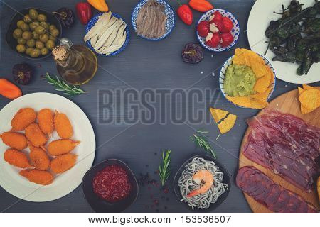 Table with spanish tapas - anchovies, peppers padron, jamon, croquetes, guacamole, hot salsa and olives, frame with copy space, retro toned