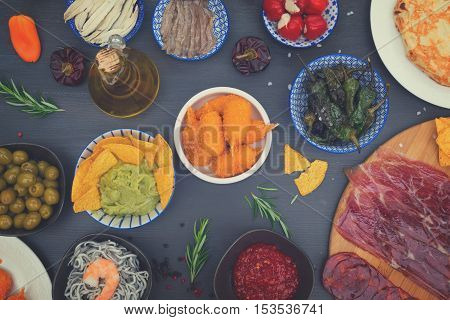 Table with spanish tapas - anchovies, green peppers padron, jamon, croquetes, guacamole and olives, top view of picnic table, retro toned