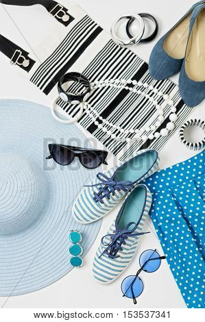 Fashion accessories in black and white and blue colors - hat clothing shoes and bag bracelets and glasses.
