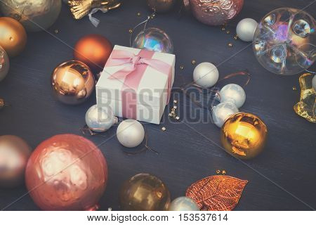 Christmas golden and silver decorations on dark wooden background with present box, retro toned