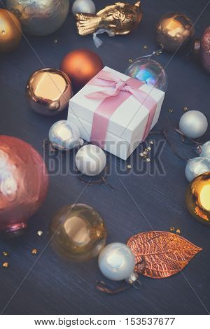 Christmas golden and silver decorations on dark wooden background with gift box, retro toned