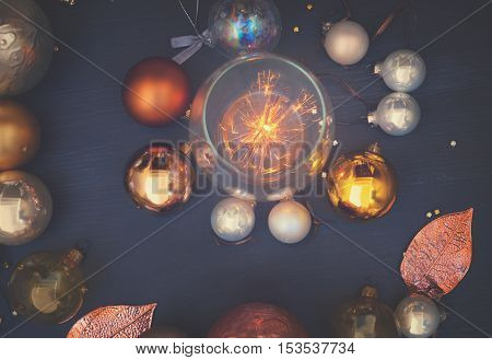 Christmas golden and silver decorations on dark wooden background with shining light, retro toned