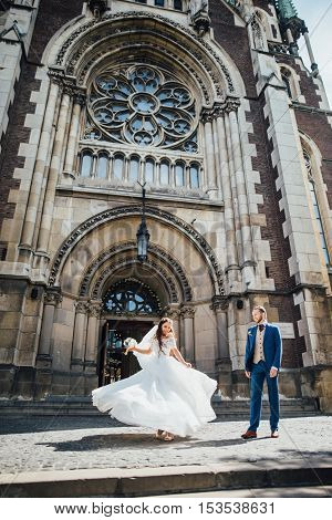 brides dancing on the background of a Gothic church and smiling