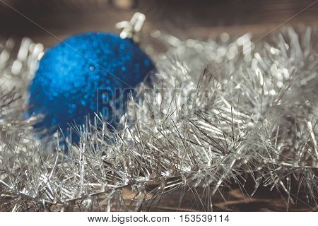 Christmas and new year background with tinsel, ball on old wooden table