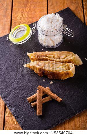 Cinnamon With Strudel And Cream On Slate Stone