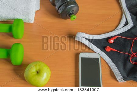 The concept of a healthy lifestyle. Apple, dumbbell, bottle towel t-shirt.