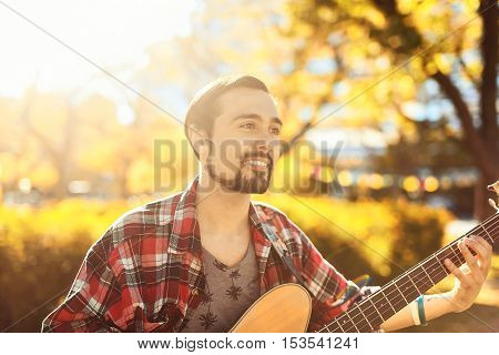 Portrait of happy hispanic young man playing bass guitar in the park at the sunny autumn background. Professions and hobbies. Lifestyle.
