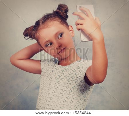Fun Kid Girl Posing And Making A Selfie Photo On Mobile Phone. Vintage Toned Portrait