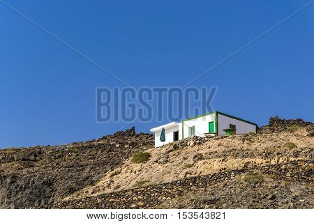 Modest home on the top of the hill, daylight scene with perfectly clear blue sky shot in a spanish fisher village on the Atlantic coast, on Fuerteventura, Canary Islands, Spain.