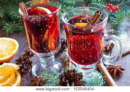 hot christmas mulled wine with snow cinnamon sticks anise and orange on wooden table background with fir branches and pine cones