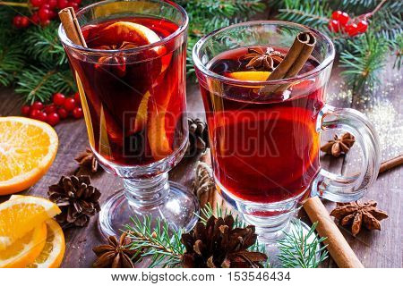 hot christmas mulled wine with cinnamon sticks anise and orange on wooden table background with fir branches and pine cones