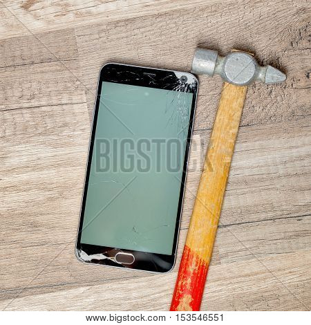 Broken phone screen on a wooden floor with an old hammer
