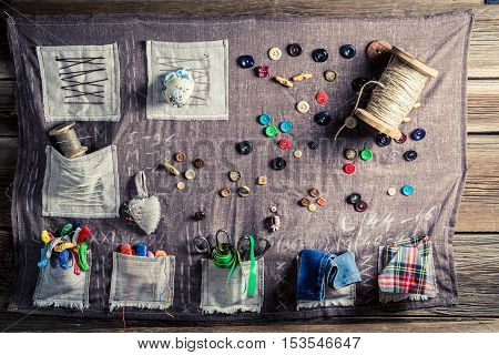 Old Sewing Cloth Made Of Threads, Needles And Buttons In Tailor Workshop