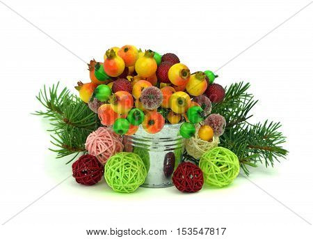 Small decorative bucket with berries balls and Christmas tree an isolation white background. Lovely decorations for the holiday.