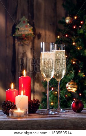 close up view of two glasses with champagne and candles on color back