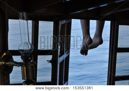 Legs dangling from the deck. Sea view through the open window.