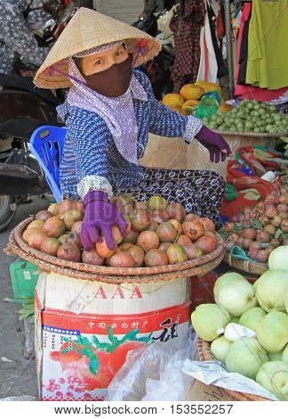Vinh, Vietnam - May 29, 2015: woman in mask is selling fruits and vegetables on street market in Vinh, Vietnam