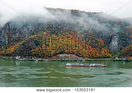 ESELNITA ROMANIA - OCTOBER 22 2016:Autumn at Danube Gorges the border between Romania and Serbia.View from Serbian part.In background the Decebal king's image carved in stone and monastery Mraconia
