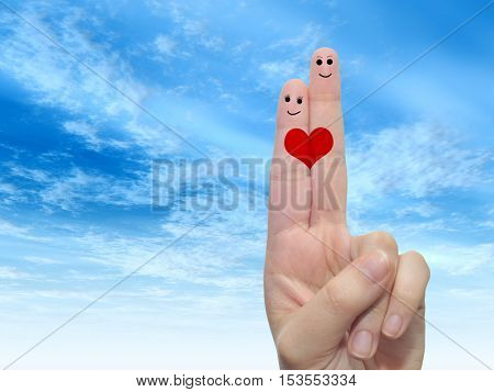 Concept or conceptual human or female hands with two fingers painted with a red heart and smiley faces over cloud blue sky background
