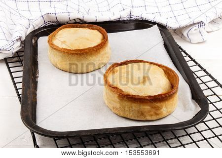 fresh and warm baked scotch pie with white baking paper on a backing tray