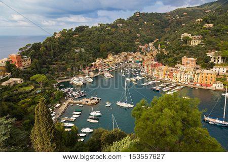 PORTOFINO, ITALY - SEPTEMBER 2016 : Restaurants, shops, colorful historical buildings, many boats at Portofino port, Italian fishing village, Genoa province, Italy on September 23, 2016.