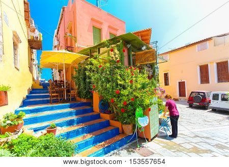 Rethymnon Island Crete Greece - July 1 2016: Cozy Cretan small cafe with flowers outside with and waitress is putting a menu on the table for visitors