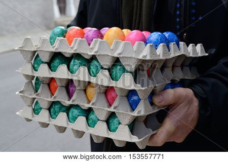 Person holds several stacks of colored eggs for Easter