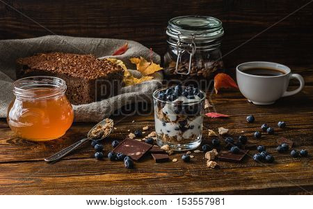 Breakfast with granola, yogurt, blueberries, honey and chocolate bars on wooden table with ingredients.
