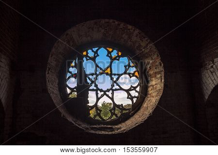 Round castle window with broken stained-glass windows