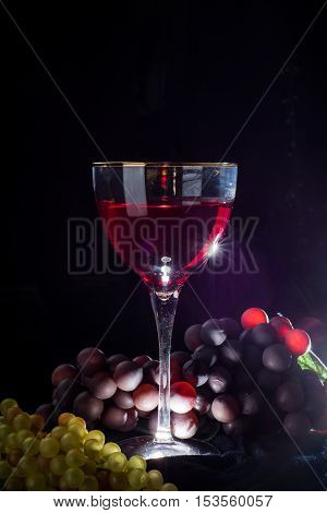 glass of red grapes on a black background