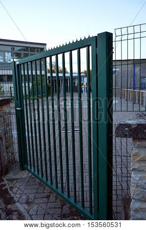 Metal railing of green color which closes enters him of a school