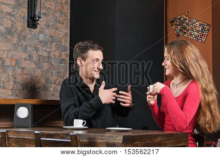 Man explains something to his girlfriend gesticulating. Couple sitting in a cafe with a cup of coffee