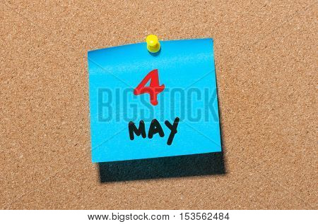 May 4th. Day 4 of month, calendar on cork notice board, business background. Spring time, empty space for text.