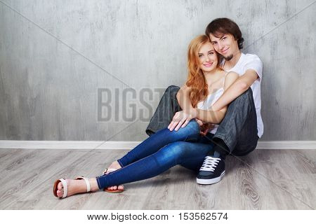 happy young beautiful couple sitting on the floor  in the studio