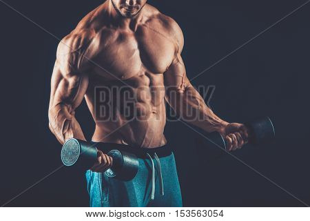 Closeup of a muscular young man lifting dumbbells weights on dark background