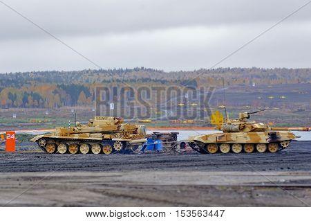 Nizhniy Tagil, Russia - September 27. 2013: Armoured recovery vehicle BREM-1M evacuates t-90S tank on exhibition range. RAE-2013 exhibition