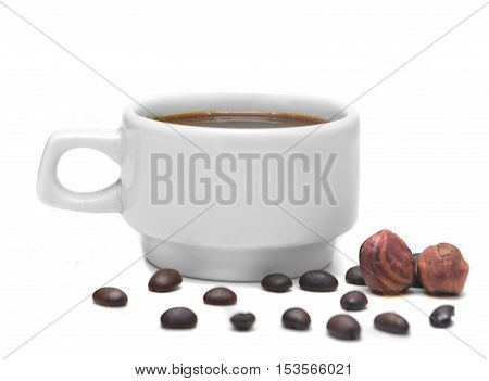 white cup of espresso on a white background decorated with coffee beans and nuts