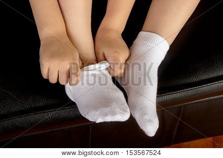 Young School Girl Student Wearing White Socks and Stting on a Leather Sofa