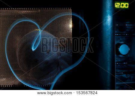 Cute ghost in the microwave in the dark. 12:00 hours on the lighting scoreboard. Halloween joke. Heart shape ghostly glow.