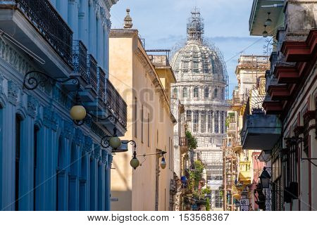 Colorful neighborhood in Old Havana with typical colonial buildings and a view of the Capitol on a beautiful summer day
