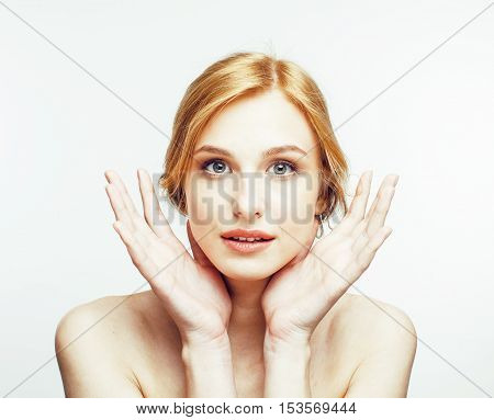 young pretty red hair woman smiling holding hands on face isolated on white background, spa health care people concept close up