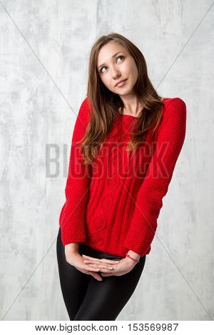 Attractive young woman posing at photostudio in red sweater